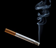 Cigarette with blue smoke on black background