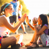 A counselor and a young camper play pattycake.